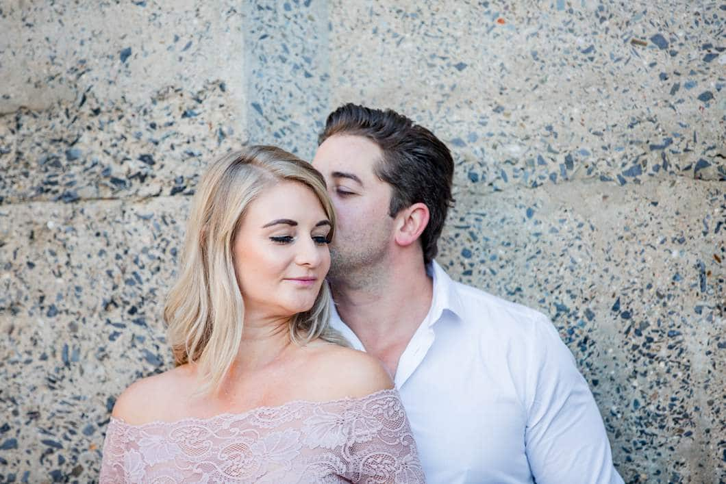 gentle kisses during an urban engagement shoot at the cape town waterfront at sunrise
