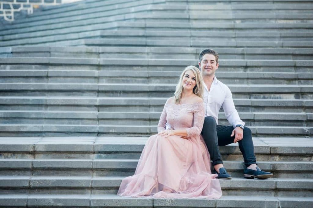 engaged couple sitting on concrete stairs in cocktail dress and suit during their photoshoot with katie mayhew